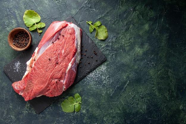 Vista superior de carne vermelha fresca crua em uma tábua de cortar pimenta em fundo de cores preto e verde.