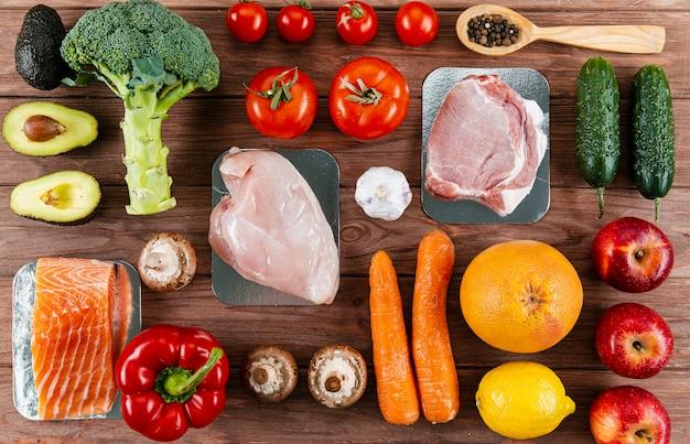 Vista superior de carnes organizadas com legumes