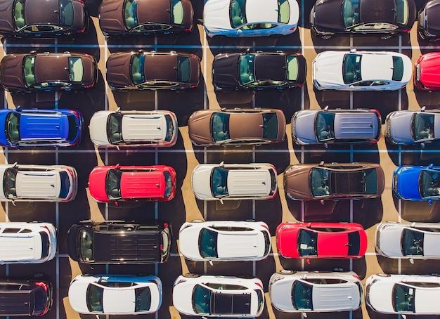 Vista superior de carros novos alinhados do lado de fora de uma fábrica de automóveis para exportação e importação.
