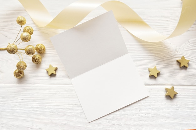Vista superior de cartão de saudação de maquete de natal e estrela de ouro, flatlay em um fundo branco de madeira com uma fita