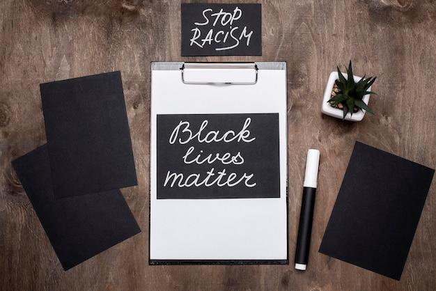 Vista superior de cartas de matéria de vidas negras com caneta e planta