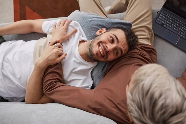 Vista superior de casal gay contemporâneo se abraçando enquanto relaxa no sofá em casa, copie o espaço