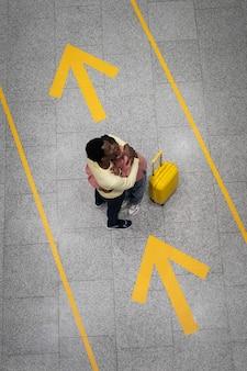 Vista superior de casal romântico se abraçando no aeroporto