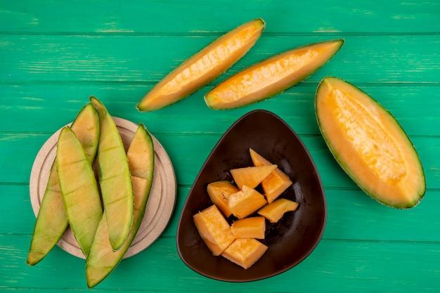 Vista superior de cascas de melão em uma placa de cozinha de madeira com fatias de melão em uma tigela marrom