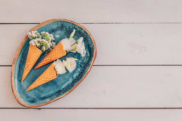 Vista superior de casquinhas de sorvete em prato antigo com flores em madeira branca