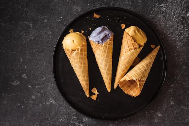 Vista superior de casquinhas de sorvete em uma grande placa preta