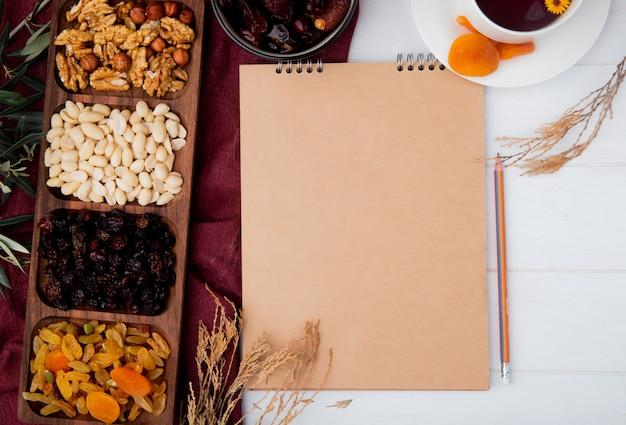 Vista superior de castanhas e frutas secas em uma caixa de madeira e um caderno de desenho em rústico