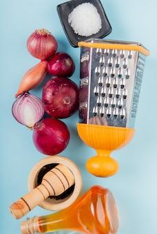 Vista superior de cebolas cortadas e inteiras com manteiga derretida, pimenta preta, sal e ralador em azul