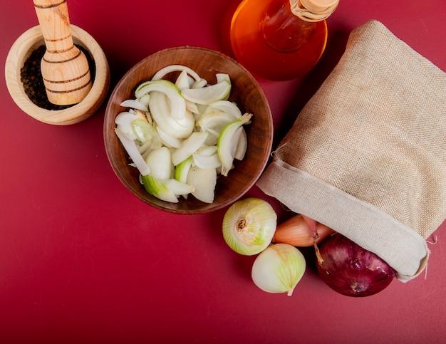 Vista superior de cebolas derramando fora do saco com fatias na tigela e manteiga derretida com sementes de pimenta preta no triturador de alho na superfície vermelha