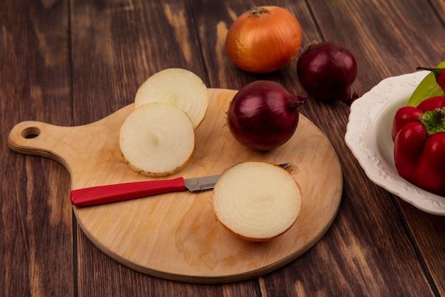 Vista superior de cebolas frescas em uma placa de cozinha de madeira com uma faca com pimentas em uma tigela na parede de madeira