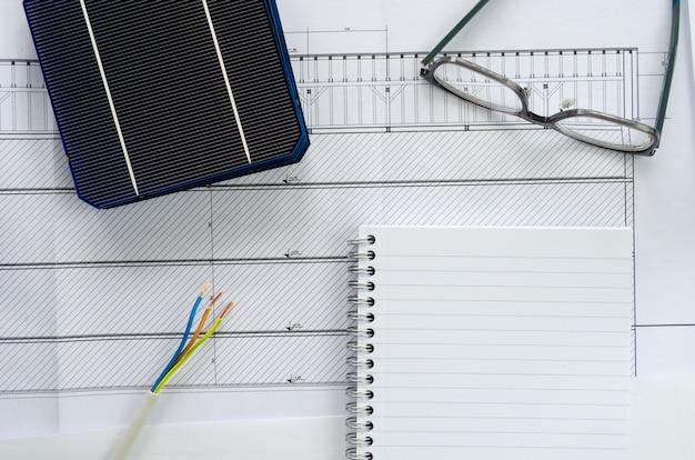 Vista superior de células solares, bloco de notas, óculos e cabo elétrico como conceito de planejamento para projeto de foto voltaica