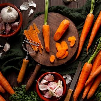 Vista superior de cenouras com descascador e alho