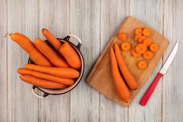 Vista superior de cenouras frescas de laranja em uma placa de cozinha de madeira com uma faca com cenouras em uma tigela sobre uma superfície cinza de madeira