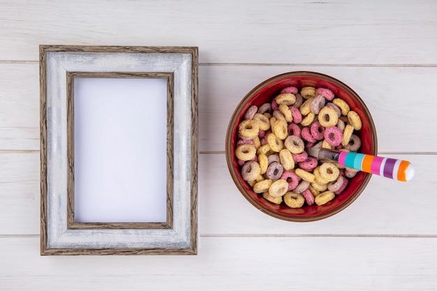 Vista superior de cereais coloridos e saudáveis em uma tigela vermelha na superfície branca