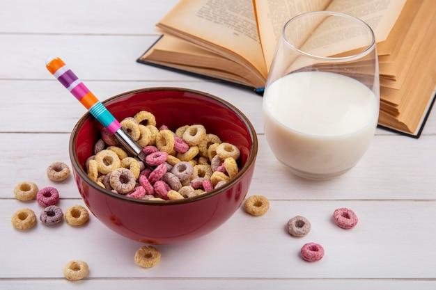 Vista superior de cereais coloridos em uma tigela vermelha com uma colher com um copo de leite em branco