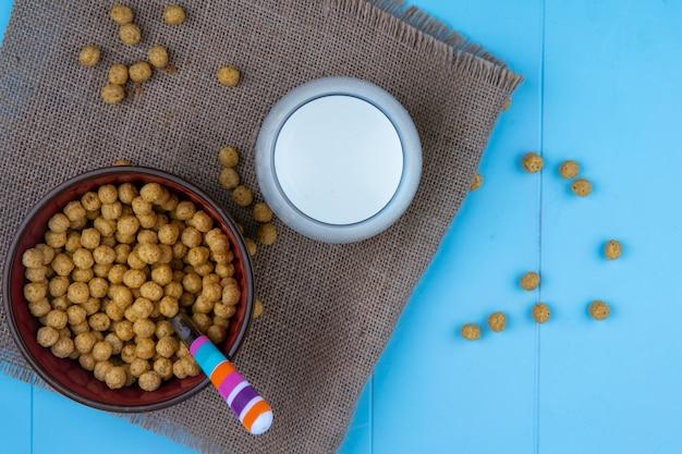Vista superior de cereais com colher na tigela e leite de saco em fundo azul