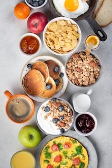 Vista superior de cereais com omelete e panquecas no café da manhã