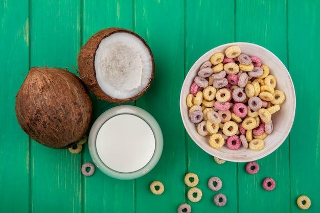 Vista superior de cereais multicoloridos em uma tigela branca com coco e leite na superfície verde