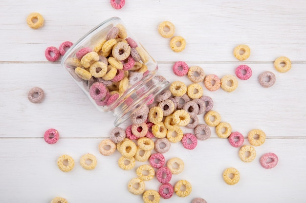 Vista superior de cereais saudáveis e coloridos em uma jarra de vidro com cereais isolados na superfície de madeira branca