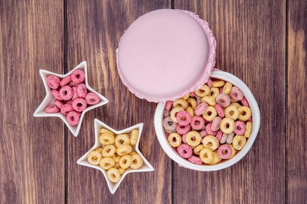 Vista superior de cereais saudáveis e loop em uma tigela de círculo branco e tigelas em forma de estrela na superfície de madeira
