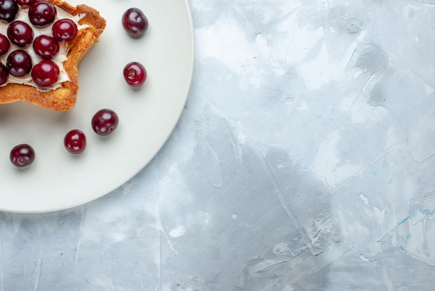 Vista superior de cerejas ácidas frescas dentro do prato com bolo cremoso em forma de estrela em branco claro