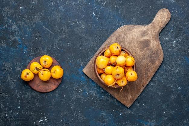Vista superior de cerejas amarelas frescas, frutas doces maduras em frutas de piso escuro, cereja doce fresca