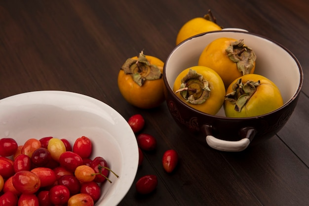 Vista superior de cerejas da cornalina em uma tigela branca com frutos de caqui amarelos em uma tigela sobre uma superfície de madeira