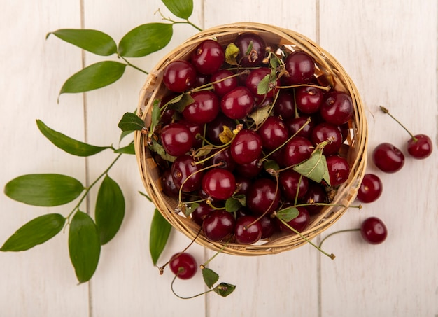 Vista superior de cerejas em uma cesta com folhas em fundo de madeira
