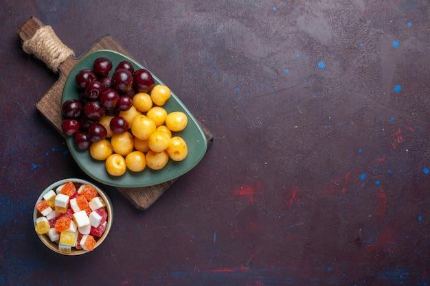 Vista superior de cerejas frescas com doces na superfície escura