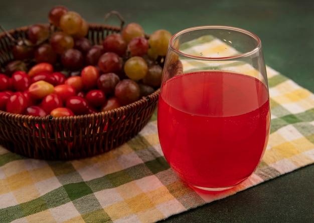 Vista superior de cerejas frescas da cornalina em um balde em um pano xadrez com uvas com suco fresco em um copo em uma superfície verde