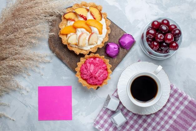 Vista superior de cerejas frescas dentro de um copinho de vidro com bolos de creme e chá na luz branca, vitamina de frutas ácidas doces