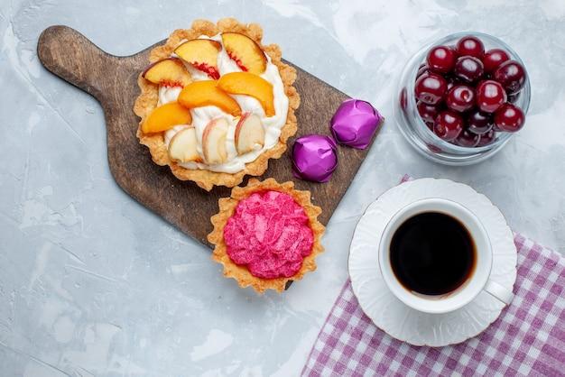 Vista superior de cerejas frescas dentro de um copinho de vidro com bolos de creme e chá na mesa com luz branca, vitamina de frutas ácidas e doces