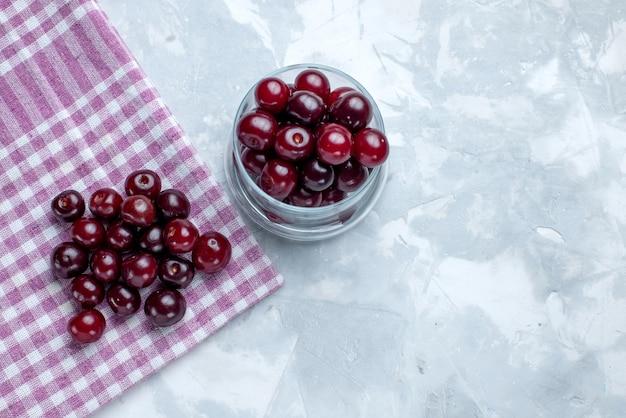 Vista superior de cerejas frescas dentro de um pequeno copo de vidro em piso claro de frutas ácidas vitamina doce