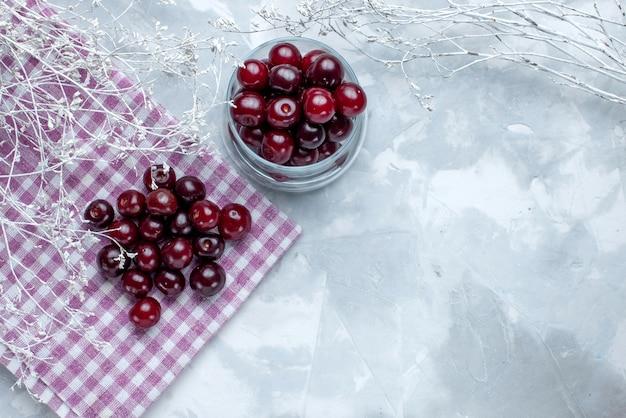 Vista superior de cerejas frescas dentro de um pequeno copo de vidro na vitamina de frutas ácidas de piso claro