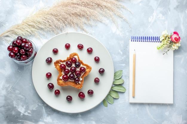 Vista superior de cerejas frescas dentro do prato com bloco de notas de bolo cremoso em forma de estrela na mesa branca, biscoito de bolo de verão com frutas azedas