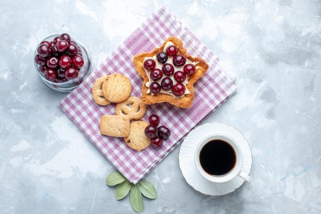Vista superior de cerejas frescas dentro do prato com bolo cremoso em forma de estrela e biscoitos na mesa branca, biscoito de bolo de frutas azedo de verão