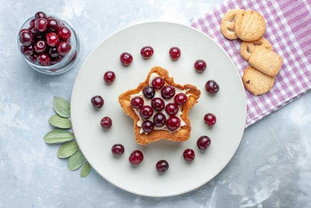 Vista superior de cerejas frescas dentro do prato com bolo cremoso em forma de estrela e biscoitos no biscoito de bolo de verão de frutas azedas branco
