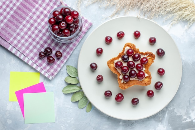 Vista superior de cerejas frescas dentro do prato com bolo cremoso em forma de estrela em uma mesa branca