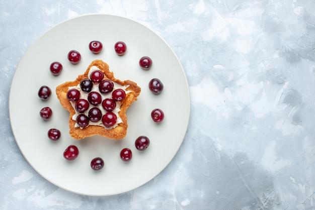 Vista superior de cerejas frescas dentro do prato com bolo cremoso em forma de estrela no verão branco claro, vitamina de frutas azedas