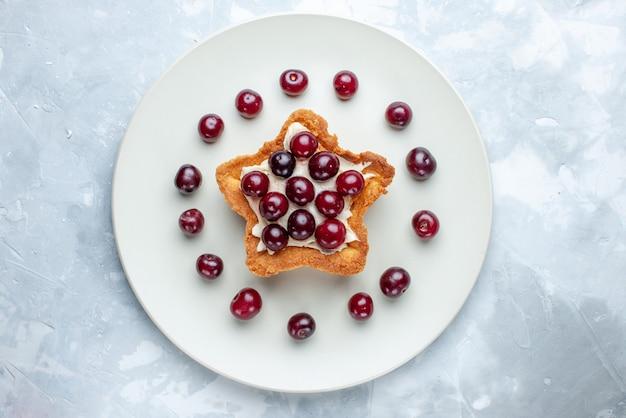 Vista superior de cerejas frescas dentro do prato com bolo em forma de estrela em uma mesa branca clara, vitamina de frutas azedas verão