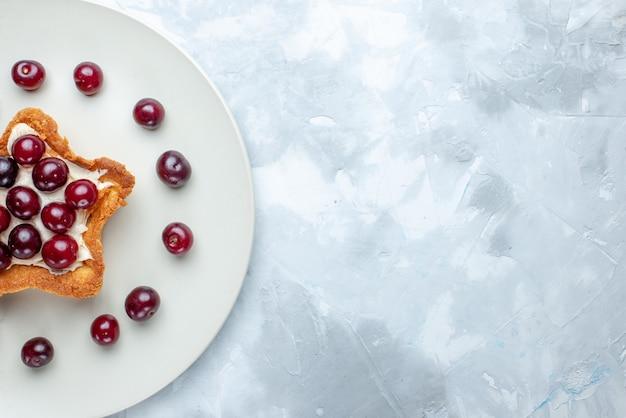 Vista superior de cerejas frescas dentro do prato com bolo em forma de estrela na mesa com luz branca, vitamina de frutas azedas no verão