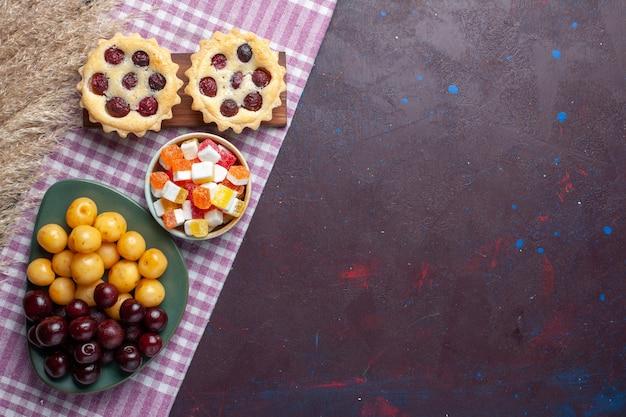 Vista superior de cerejas frescas dentro do prato com bolos e doces na superfície escura
