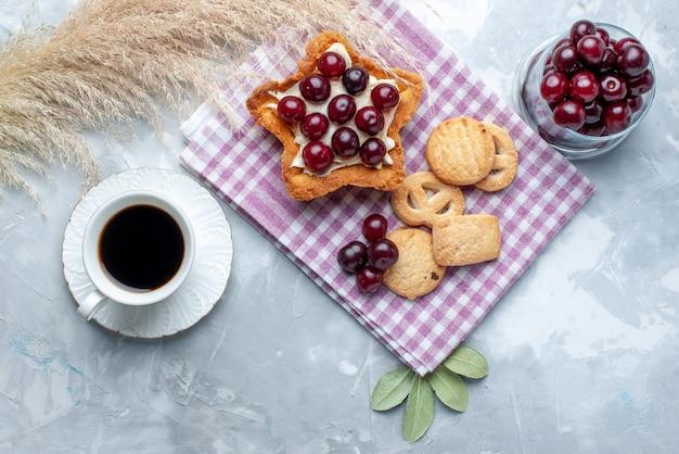 Vista superior de cerejas frescas dentro do prato com chá de bolo cremoso em forma de estrela e biscoitos em um biscoito de verão com luz branca e azedo de frutas