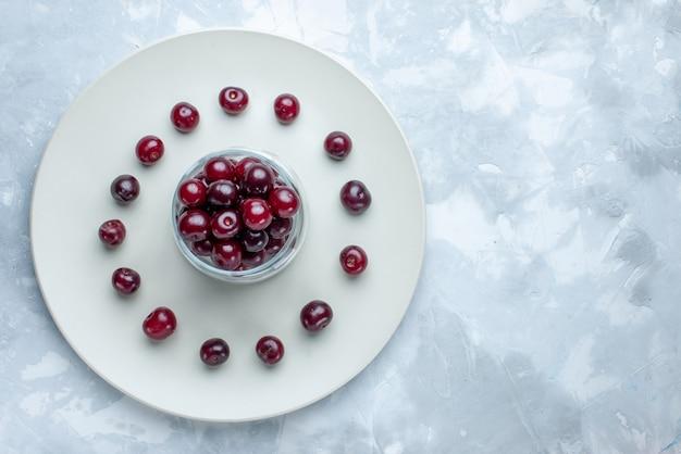 Vista superior de cerejas frescas dentro do prato na mesa iluminada, vitamina de frutas azedas frutas frescas no verão