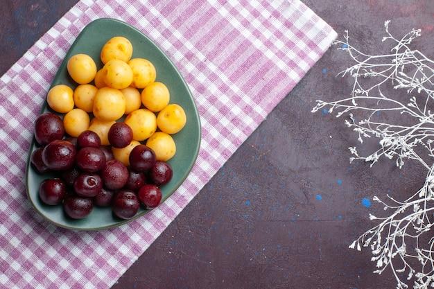 Vista superior de cerejas frescas dentro do prato na superfície escura