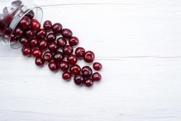 Vista superior de cerejas frescas inteiras e maduras em suco de frutas claras e maduras