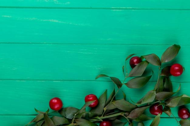 Vista superior de cerejas maduras vermelhas com folhas verdes em madeira verde com espaço de cópia