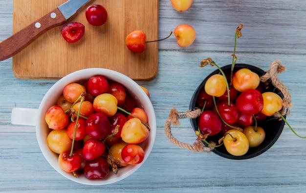 Vista superior de cerejas maduras vermelhas e amarelas em um balde e cerejas mais chuvosas em uma tigela de madeira rústica