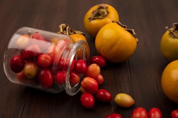 Vista superior de cerejas vermelhas da cornalina caindo de uma jarra de vidro com frutas de caqui isoladas em uma superfície de madeira