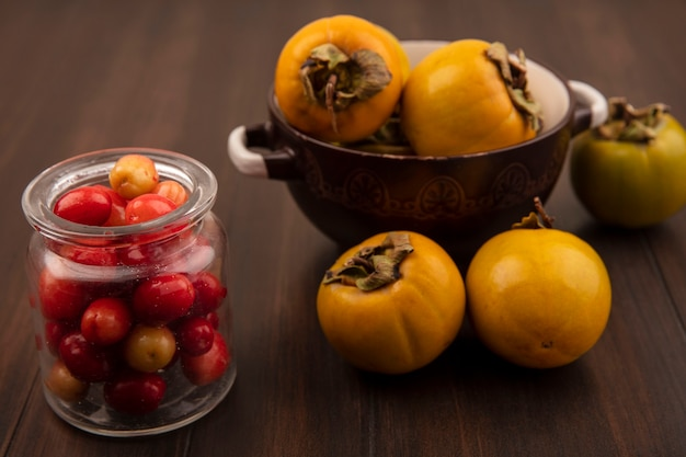 Vista superior de cerejas vermelhas da cornalina em uma jarra de vidro com frutas de caqui em uma tigela sobre uma superfície de madeira